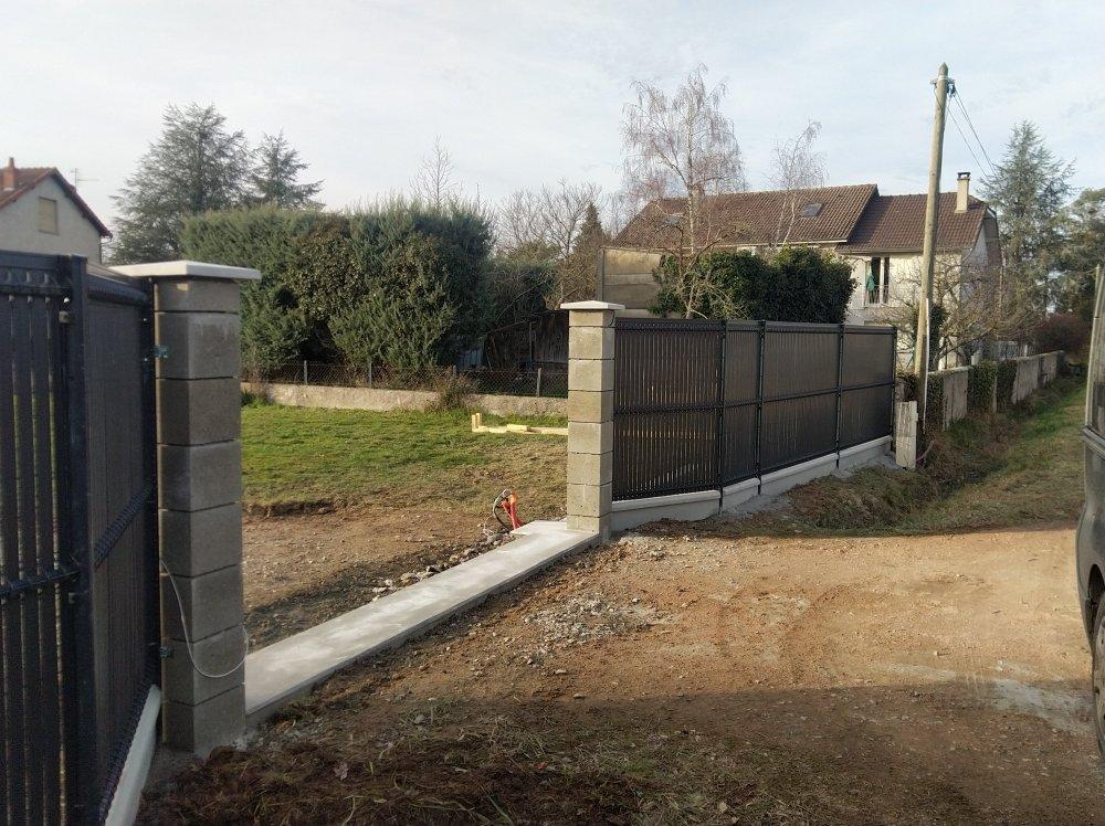 Clotûre rigide Bétafence gris anthracite avec occultants intégrés et sous-bassement béton à Montlucon + maconnerie seuil portail.